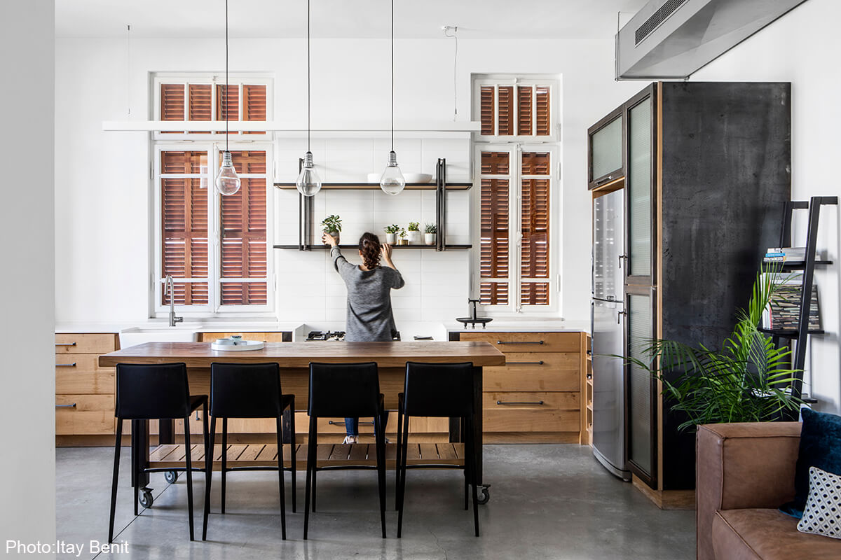 Wooden modern kitchen in apartment in an old preserved building next to the Carmel market. In the most hectic area in Tel Aviv this home was meant to serve as a serene haven. Clean lines, concrete floors and bare materials compliment the high ceiling and large wooden windows of the historic building, designed by Adi Mor Architect - Fineshmaker