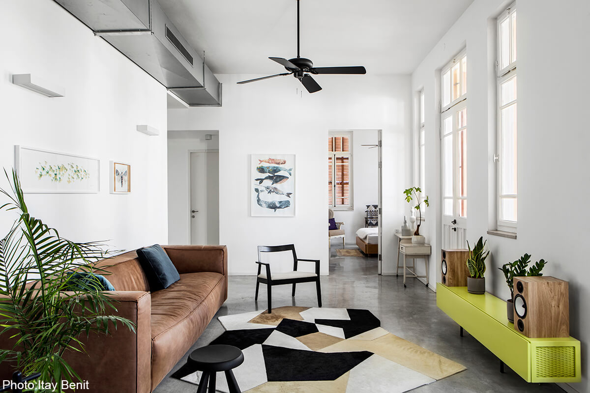 Modern living room in apartment in an old preserved building next to the Carmel market. In the most hectic area in Tel Aviv this home was meant to serve as a serene haven. Clean lines, concrete floors and bare materials compliment the high ceiling and large wooden windows of the historic building.