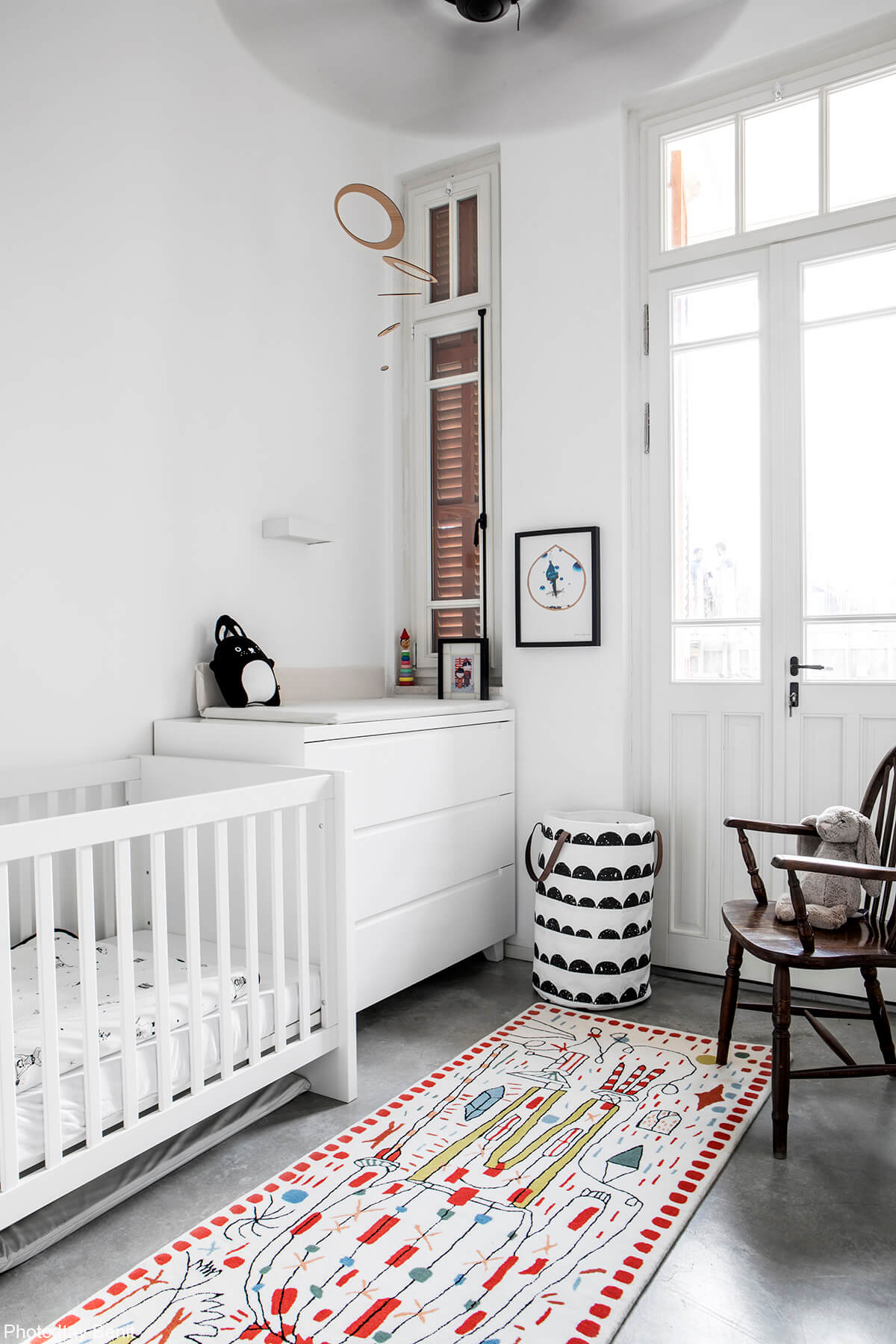 Children room in Modern apartment in an old preserved building next to the Carmel market. In the most hectic area in Tel Aviv this home was meant to serve as a serene haven. Clean lines, concrete floors and bare materials compliment the high ceiling and large wooden windows of the historic building, designed by Adi Mor Architect - Fineshmaker