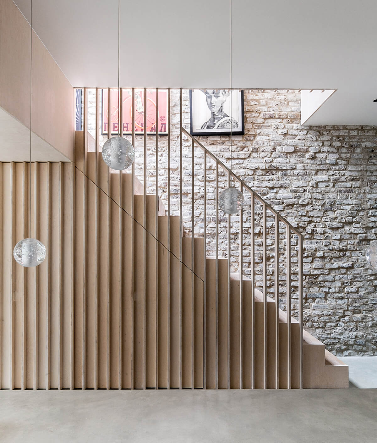 A plywood staircase with vertical slats leads to the first floor.